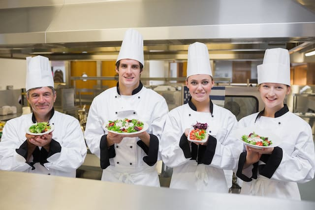Chef's presenting different salads in the kitchen