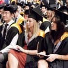 students_sitting_yellow_graduation_robes_INT_feature